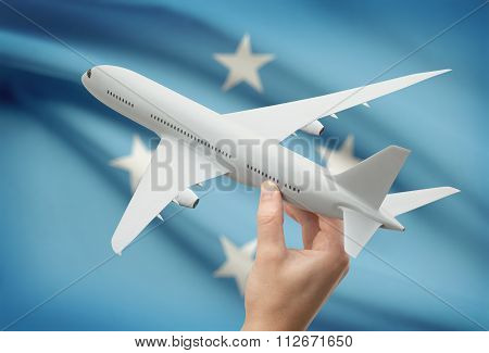 Airplane In Hand With Flag On Background - Micronesia