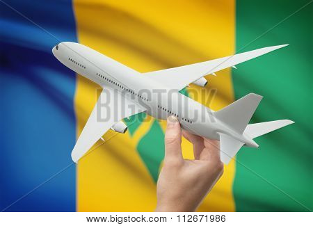Airplane In Hand With Flag On Background - Saint Vincent And The Grenadines