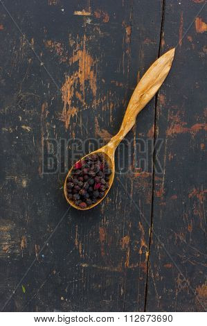 Dried hawthorn berries in a wooden spoon