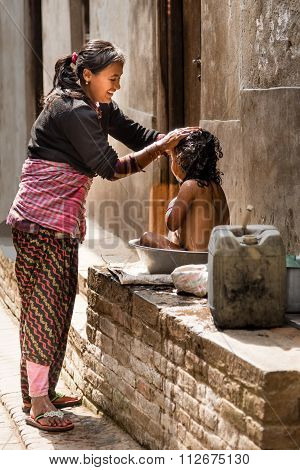 Bhaktapur Street Life, A Girl Being Washed By Mother.
