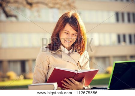 Student girl learning preparing for an exam in campus.