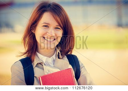 Young smiling student professional outdoors holding a red book.
