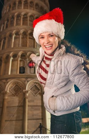 Young Woman Decorating Leaning Tower Of Pisa With Christmas Ball