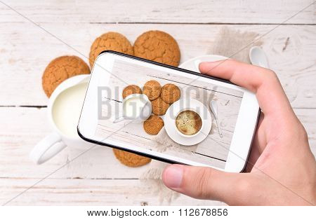 Hands taking photo coffe with smartphone