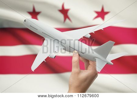 Airplane In Hand With Us State Flag On Background - District Of Columbia