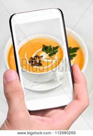Hands taking photo pumpkin soup with smartphone