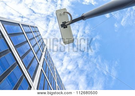 spy on pole near modern building in blue sky