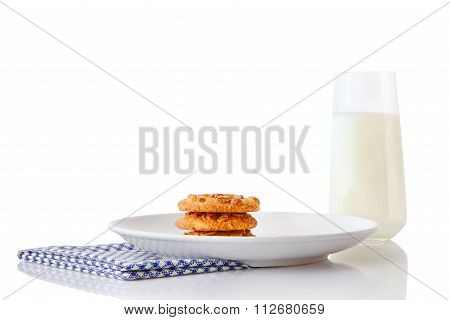 Stack of three homemade peanut butter cookies on white ceramic plate on napkin and glass of milk