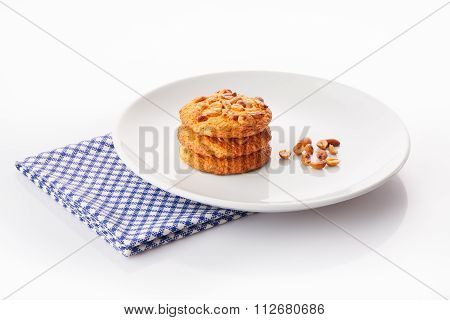 Stack of three homemade peanut butter cookies and peanuts on white ceramic plate on blue napkin