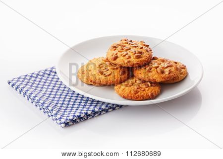 Pile of homemade peanut butter cookies on white ceramic plate on blue napkin