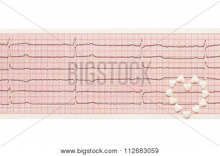 Heart made of white heart shape tablets on paper ECG results