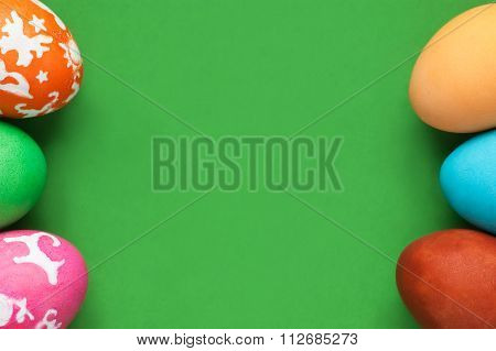 Six Colored Easter Eggs At Sides Of Frame Against Green Background