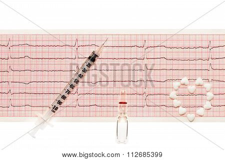 Heart made of white tablets, ampoule with a drug, plastic syringe on paper ECG results