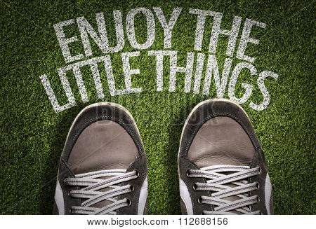 Top View of Sneakers on the grass with the text: Enjoy the Little Things