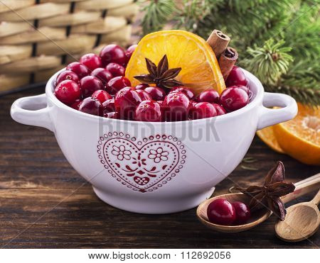 Cranberries with orange, cinnamon and star anise in a white ceramic
