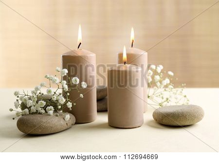 Beautiful composition of alight candles with pebbles and flowers on the table