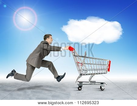 Running businessman with empty shopping cart