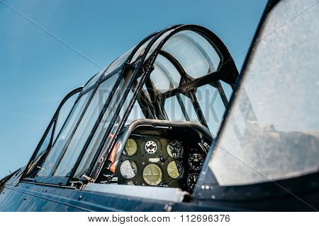 Open vintage airplane cockpit, blue sky background.