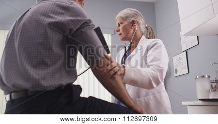 Doctor Checking Blood Pressure Of Middle-aged Male Patient