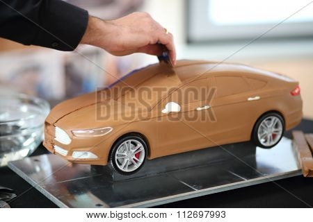RUSSIA, MOSCOW - 4 DEC, 2014: Man is smoothing with the metal plate roof of car model at press event for Ford in SREDA loft.