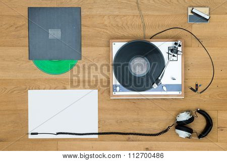 Directly above shot of headphones with retro turntable and records on wooden table