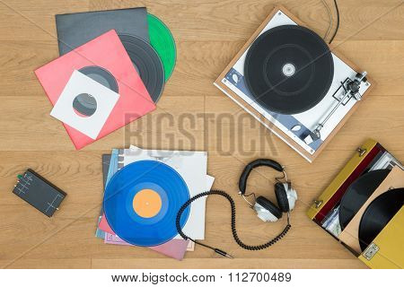 Directly above view of various records with turntable and headphones on table