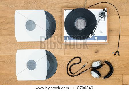 Directly above shot of vintage turntable and records on wooden table