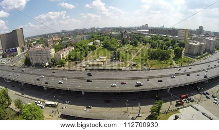 RUSSIA, MOSCOW - MAY 24, 2014: City traffic on street near hotel Cosmos and skyscrapers of Moscow business center at sunny spring day. Aerial view