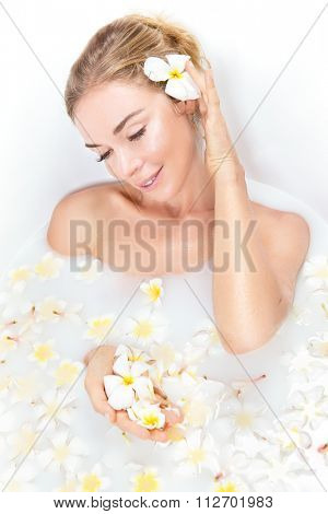 Woman beauty spa and wellness treathment with white flower petals in bath with milk