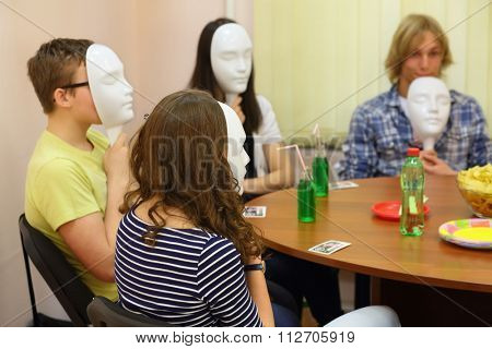 Four young people play Mafia with masks at the table in the classroom