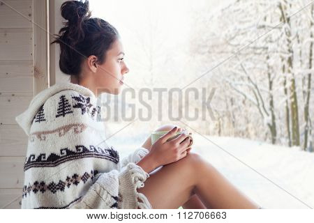 Young beautiful happy brunette woman drinking cup of coffee wearing knitted nordic print poncho chilling out home by the window. Winter forrest landscape background.