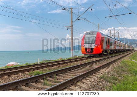 red train rides on rails along the seashore