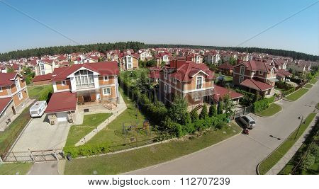Aerial view of cottage town near forest at the sunny summer day.