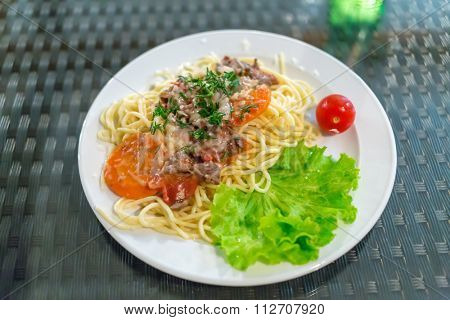 plate of pasta with meat, vegetables and lettuce