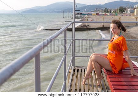 woman sitting on a lounger on a pier