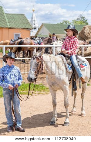 cowboy brother holds the horse of his sister by the reins