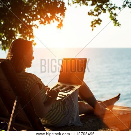 Silhouette girl c laptop sitting on a lounger near the sea in the sunset.