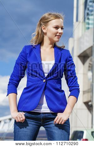 Portrait close up of young beautiful blond woman in blue jacket, on blue sky background
