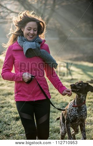 Runner woman and her cute German pointer dog running together outdoor at the beautiful park.