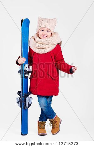 Portrait Of Cute Happy Boy Holding Skis In Hands