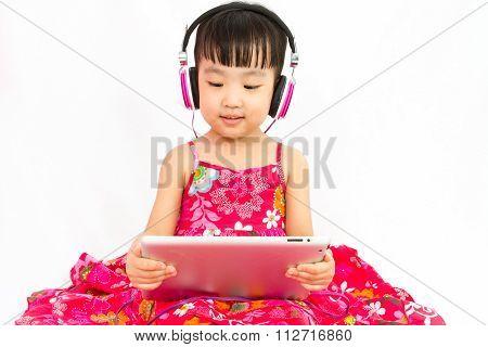 Chinese Little Girl On Headphones Holding Tablet