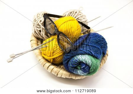 Three ball of woolen threads, yellow, blue, beige and steel knitting needles and glasses in a wooden basket on a white background