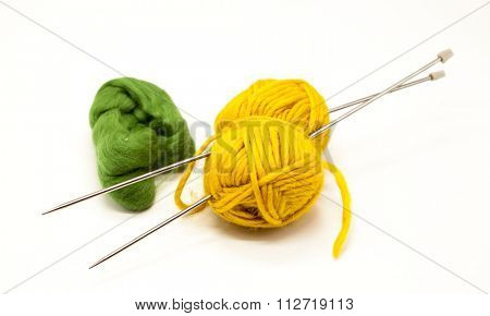 Green and yellow balls of yarn for knitting with spokes on a white background