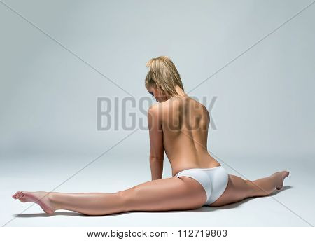 Rear view of topless woman doing gymnastic split