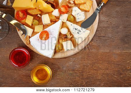 Cheese for tasting on wooden background, top view