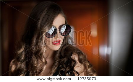 Woman with black sunglasses  and long curly hair. Beautiful woman portrait. Fashion art photo