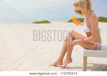 Woman sunbathing in bikini and applying sunscreen