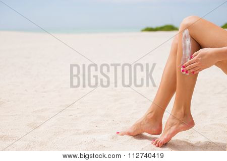 Woman applying sunscreen on her legs