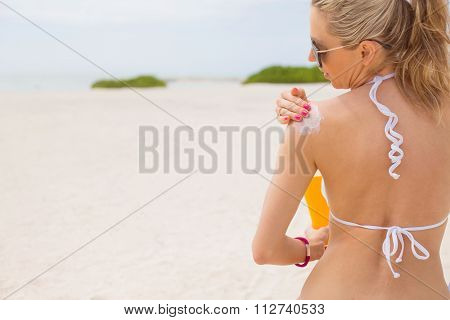 Woman applying sunscreen on the beach