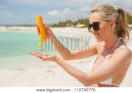 Woman using sunscreen on the beach